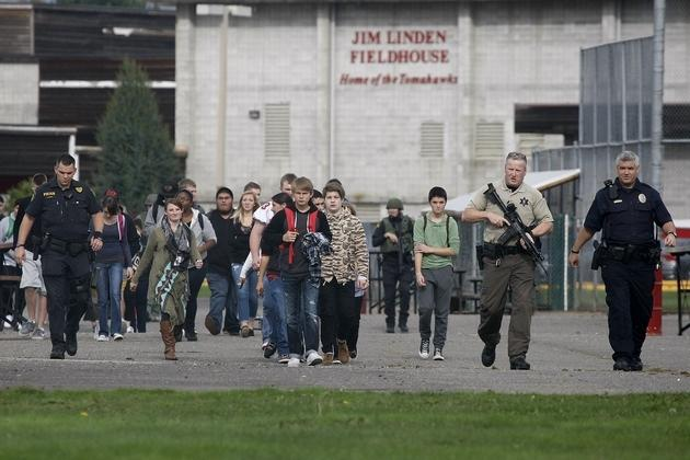 Students are evacuated from Marysville-Pilchuck High School by law enforcement officers following a shooting at the school on Friday morning.