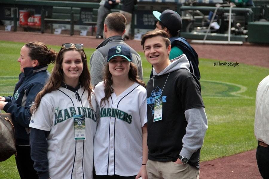 Rachel Hunter (17), Megan Chapman (16), and Edward Radion (17) celebrate on the field after Chapmans first pitch.
