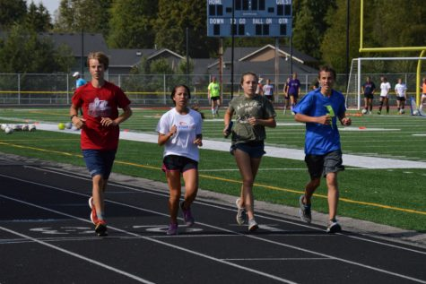 Dawson Andrews ('18), Vivian Potong ('20), Kelsey Lee ('19) and Brian Barene ('20) run together during the Arlington Cross Country's twelve hour relay event August 29. The team went on to raise upwards of 4,000 dollars.