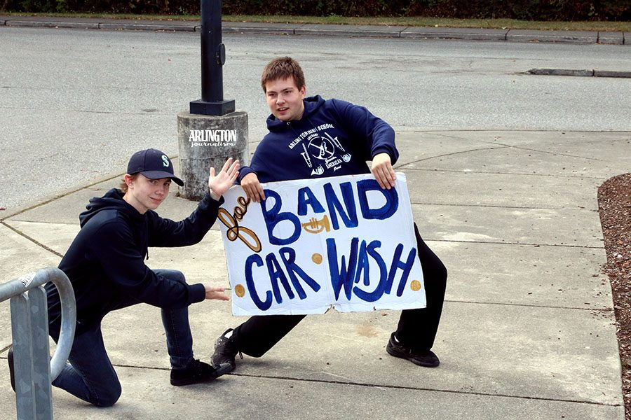 The+AHS+band+holds+an+annual+car+wash+in+the+high+school+parking+lot+to+help+raise+funds+for+their+activities.+Jacob+Hurst+%28%2720%29+and+Gavin+Gray+%28%2718%29+hold+signs+to+advertise+to+the+community+about+the+event.