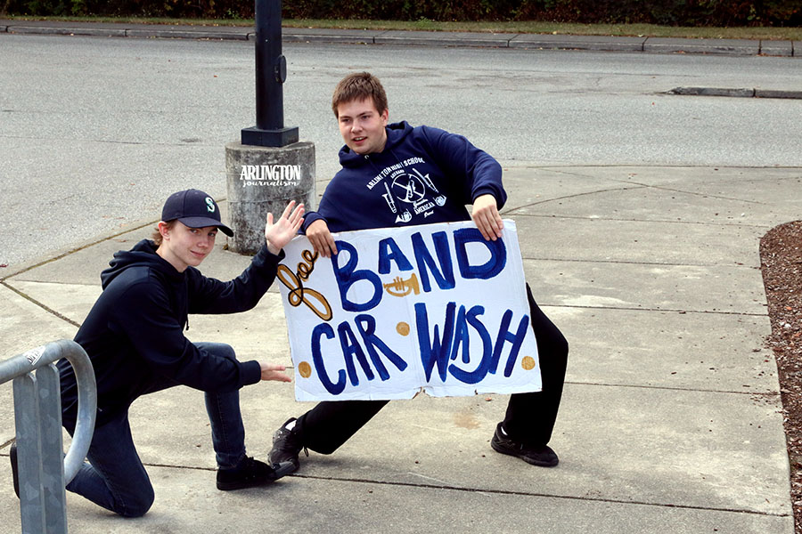 The AHS band holds an annual car wash in the high school parking lot to help raise funds for their activities. Jacob Hurst ('20) and Gavin Gray ('18) hold signs to advertise to the community about the event.