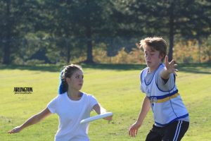 Hailey Pawley (11) throws a frisbee while Sam Schroeder (10) defends.