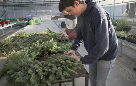 Simon Fuentes, 10th Grade, is creating a wreath for the FFA's club fundraiser.