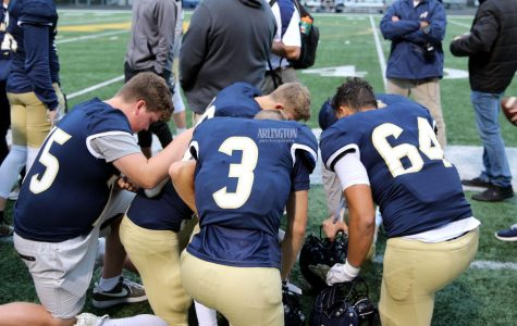 Luke Zachman (11), Andrew Brotherton (11), and Quintin Yon-Wagner (10) kneel before their game to pray.