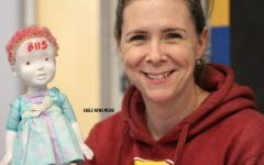 Ms. Perrigo holds up her bathroom pass which happens to be a possessed baby doll.
