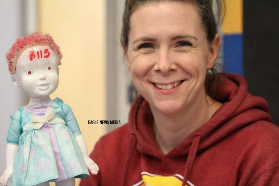 Ms.+Perrigo+holds+up+her+bathroom+pass+which+happens+to+be+a+possessed+baby+doll.